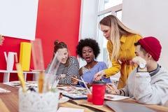 Νέος δάσκαλος τέχνης που αντιπαθεί τα αποτελέσματα της εργασίας των σπουδαστών της στοκ εικόνα