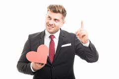 Νέος διευθυντής που κρατά την κόκκινη μορφή καρδιών δείχνοντας επάνω Στοκ Εικόνες
