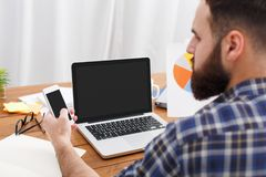 Νέος διευθυντής ΤΠ γενειάδων που εξετάζει στο κινητό τηλέφωνο την εργασία με τον υπολογιστή Στοκ Φωτογραφίες