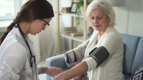 Νέος ειδικός που μετρά τη πίεση του αίματος στον ασθενή της στο σπίτι απόθεμα βίντεο
