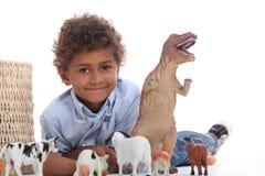 Νέος δεινόσαυρος παιχνιδιού αγοριών Στοκ φωτογραφίες με δικαίωμα ελεύθερης χρήσης