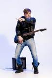 Νέος εκφραστικός μουσικός βράχου που παίζει την ηλεκτρική κιθάρα και το τραγούδι Αστέρας της ροκ που κάνει τη χειρονομία βράχου Στοκ Φωτογραφίες