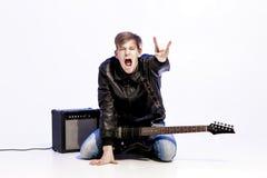 Νέος εκφραστικός μουσικός βράχου που παίζει την ηλεκτρική κιθάρα και το τραγούδι Αστέρας της ροκ που κάνει τη χειρονομία βράχου Στοκ Εικόνα