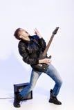Νέος εκφραστικός μουσικός βράχου που παίζει την ηλεκτρική κιθάρα και το τραγούδι Αστέρας της ροκ που κάνει τη χειρονομία βράχου Στοκ Φωτογραφία