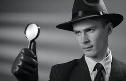 Νέος εκλεκτής ποιότητας ιδιωτικός αστυνομικός που κρατά μια ενίσχυση - γυαλί Στοκ εικόνα με δικαίωμα ελεύθερης χρήσης