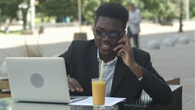 Νέος ελκυστικός αμερικανικός επιχειρηματίας afro με τα γυαλιά και συνεδρίαση lap-top στο φραγμό καφέδων και ομιλία στο τηλέφωνο κ απόθεμα βίντεο