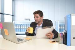 Νέος ελκυστικός επιχειρηματίας που απασχολείται ευτυχή σε βέβαιο στο γραφείο με το φορητό προσωπικό υπολογιστή και τη γραφική εργ στοκ εικόνες