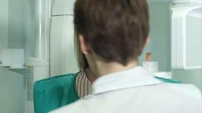Νέος ελκυστικός θηλυκός ασθενής που προετοιμάζεται για την οδοντική ανίχνευση ακτίνας X φιλμ μικρού μήκους