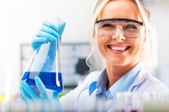 Νέος ελκυστικός θηλυκός επιστήμονας που κρατά μια φιάλη με το μπλε liqu Στοκ φωτογραφίες με δικαίωμα ελεύθερης χρήσης