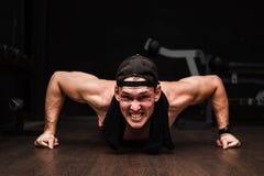 Νέος ενήλικος αθλητής που κάνει την ώθηση UPS ως τμήμα της κατάρτισης Bodybuilding στοκ εικόνες
