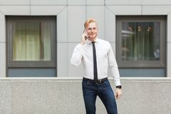 Νέος ενήλικος επιχειρηματίας που καλεί τον προϊστάμενό του, την εξέταση τη κάμερα και το χαμόγελο Στοκ Εικόνα