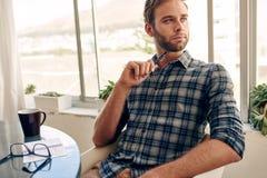 Νέος ενήλικος αρσενικός επιχειρηματίας που κοιτάζει από τη κάμερα Στοκ Φωτογραφία