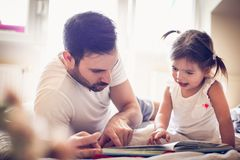 Νέος ενιαίος πατέρας που οδηγά το παραμύθι μικρών κοριτσιών του στοκ φωτογραφίες