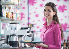 Νέος εξυπηρετώντας καφές σερβιτορών χαμόγελου στο φραγμό Στοκ Εικόνες