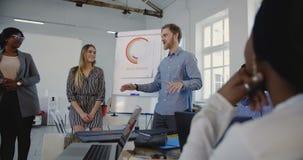 Νέος επαγγελματικός ενεργητικός επιχειρηματίας που παρακινεί τους ευτυχείς multiethnic εταιρικούς υπαλλήλους στην επίσημη συνεδρί φιλμ μικρού μήκους