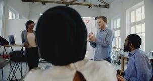 Νέος επαγγελματικός ευτυχής καυκάσιος επιχειρηματίας που οδηγεί τους ευτυχείς multiethnic εταιρικούς υπαλλήλους στο σεμινάριο ομά απόθεμα βίντεο