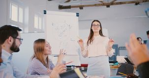 Νέος επαγγελματικός θηλυκός σταθερός εμπειρογνώμονας νόμου στα γυαλιά που μοιράζεται την εμπειρία με τους multiethnic εργαζομένου φιλμ μικρού μήκους