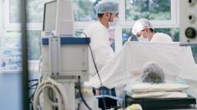 Νέος επαγγελματικός χειρούργος δύο που συζητά να προετοιμαστεί στη λειτουργία στο σύγχρονο λειτουργούν δωμάτιο φιλμ μικρού μήκους