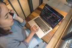 Νέος επενδυτής χρησιμοποιώντας το τηλέφωνο και ελέγχοντας το χρηματιστήριο Στοκ φωτογραφίες με δικαίωμα ελεύθερης χρήσης