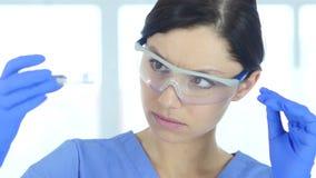 Νέος επιστήμονας που εξετάζει την μπλε λύση στο σωλήνα δοκιμής στο εργαστήριο απόθεμα βίντεο