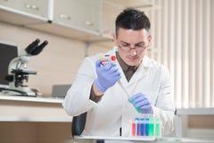 Νέος επιστήμονας που εργάζεται με τα υγρά υλικά Στοκ εικόνες με δικαίωμα ελεύθερης χρήσης