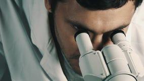 Νέος επιστήμονας που κοιτάζει μέσω του μικροσκοπίου απόθεμα βίντεο