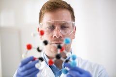 Νέος επιστήμονας που κρατά το μοριακό πρότυπο στην ιδιωτική κλινική Στοκ Εικόνες