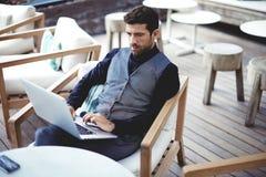 Νέος επιτυχής επιχειρηματίας που εργάζεται σε ένα lap-top καθμένος στον καφέ κατά τη διάρκεια του μεσημεριανού γεύματος σπασιμάτω Στοκ Εικόνες