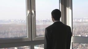 Νέος επιτυχής επιχειρηματίας που στέκεται μπροστά από τα παράθυρα που εξετάζουν την απόσταση στην πόλη o 3840x2160 απόθεμα βίντεο