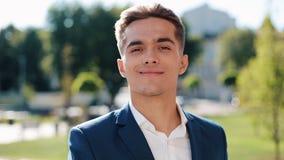 Νέος επιτυχής επιχειρηματίας στα γυαλιά ηλίου που στέκονται υπαίθρια Βγάζει τα γυαλιά του και να εξετάσει τη κάμερα απόθεμα βίντεο