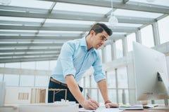 Νέος επιχειρηματίας ή αρχιτέκτονας με το πρότυπο μιας στάσης σπιτιών στην αρχή, εργασία στοκ φωτογραφίες