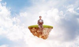 Νέος επιχειρηματίας ή σπουδαστής που επιπλέει στον ουρανό και που μελετά την επιστήμη Στοκ Εικόνες
