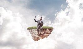 Νέος επιχειρηματίας ή σπουδαστής που επιπλέει στον ουρανό και που μελετά το Sc Στοκ εικόνες με δικαίωμα ελεύθερης χρήσης