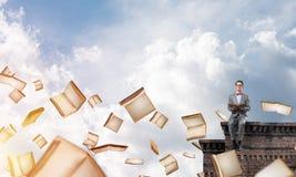 Νέος επιχειρηματίας ή σπουδαστής που μελετά την επιστήμη και τα βιβλία που πετούν γύρω Στοκ Φωτογραφίες