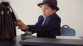 Νέος επιχειρηματίας αγοριών που προσπαθεί να ανοίξει το χαρτοφύλακα στον πίνακα εργασίας στην αρχή Χαριτωμένο αγόρι όπως χαρτοφύλ φιλμ μικρού μήκους