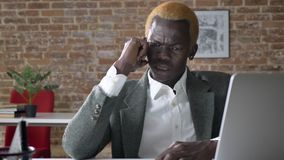 Νέος 0 επιχειρηματίας αφροαμερικάνων που μιλά στο τηλέφωνο, που κάθεται στο σύγχρονο γραφείο, σοβαρός και εξαγριωμένος φιλμ μικρού μήκους