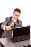 Νέος επιχειρηματίας με ένα σφυρί έτοιμο να συνθλίψει το lap-top του ενώ Στοκ Φωτογραφίες