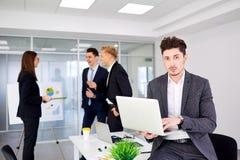 Νέος επιχειρηματίας με ένα lap-top στα χέρια των εργασιών στο backgr Στοκ φωτογραφίες με δικαίωμα ελεύθερης χρήσης