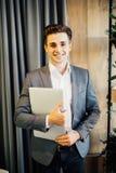 Νέος επιχειρηματίας με ένα lap-top στον περίπατο χεριών στο σύγχρονο γραφείο Στοκ εικόνες με δικαίωμα ελεύθερης χρήσης