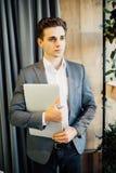 Νέος επιχειρηματίας με ένα lap-top στον περίπατο χεριών στο σύγχρονο γραφείο Στοκ Εικόνες