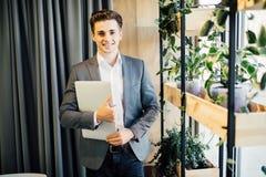 Νέος επιχειρηματίας με ένα lap-top στον περίπατο χεριών στο σύγχρονο γραφείο Στοκ Εικόνα