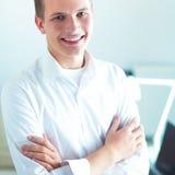 Νέος επιχειρηματίας με τα διπλωμένα όπλα που στέκονται στο γραφείο Στοκ Εικόνα