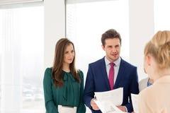 Νέος επιχειρηματίας με τη γυναίκα συνάδελφοι που συζητά πέρα από τα έγγραφα στο νέο γραφείο Στοκ εικόνες με δικαίωμα ελεύθερης χρήσης