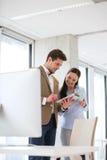 Νέος επιχειρηματίας με τη γυναίκα συνάδελφος που χρησιμοποιεί την ψηφιακή ταμπλέτα στην αρχή Στοκ φωτογραφία με δικαίωμα ελεύθερης χρήσης