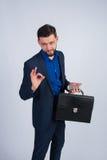 Νέος επιχειρηματίας με το τηλέφωνο και χαρτοφύλακας που παρουσιάζει εντάξει Στοκ εικόνα με δικαίωμα ελεύθερης χρήσης