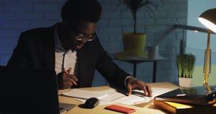 Νέος επιχειρηματίας με το φορητό προσωπικό υπολογιστή και έγγραφα που λειτουργούν αργά τη νύχτα το γραφείο Επιχείρηση, workaholic απόθεμα βίντεο