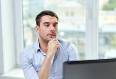 Νέος επιχειρηματίας με το φορητό προσωπικό υπολογιστή στο γραφείο Στοκ Εικόνες