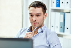Νέος επιχειρηματίας με το φορητό προσωπικό υπολογιστή στο γραφείο Στοκ φωτογραφία με δικαίωμα ελεύθερης χρήσης