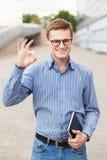 Νέος επιχειρηματίας με το jotter που παρουσιάζει ο.κ. από τα δάχτυλα Στοκ Εικόνες