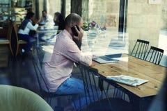 Νέος επιχειρηματίας που έχει το μεσημεριανό γεύμα σε ένα εστιατόριο και που μιλά στο τηλέφωνο που λύνει τα επιχειρησιακά ζητήματα Στοκ Φωτογραφία